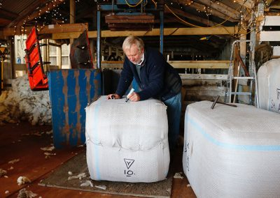 The wool is pressed into bales ready for shipping to the UK